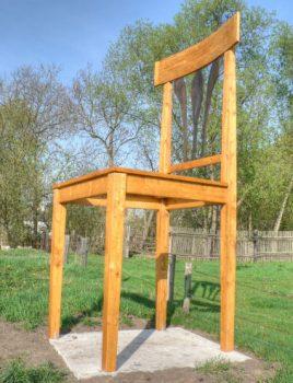Das Holz eines Stuhl schleifen