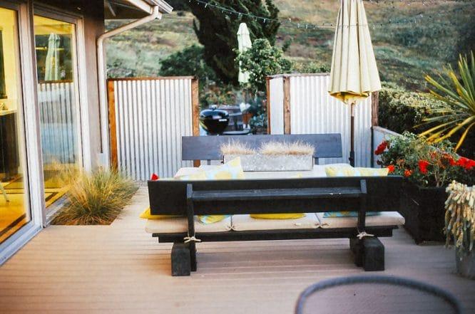 Gemütliche Gartenecke gestalten mit Bänken, Lichterkette und Sichtschutz ringsum